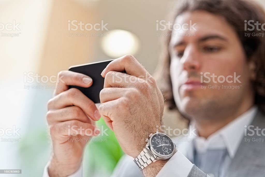 Businessman sending message on a smart phone royalty-free stock photo