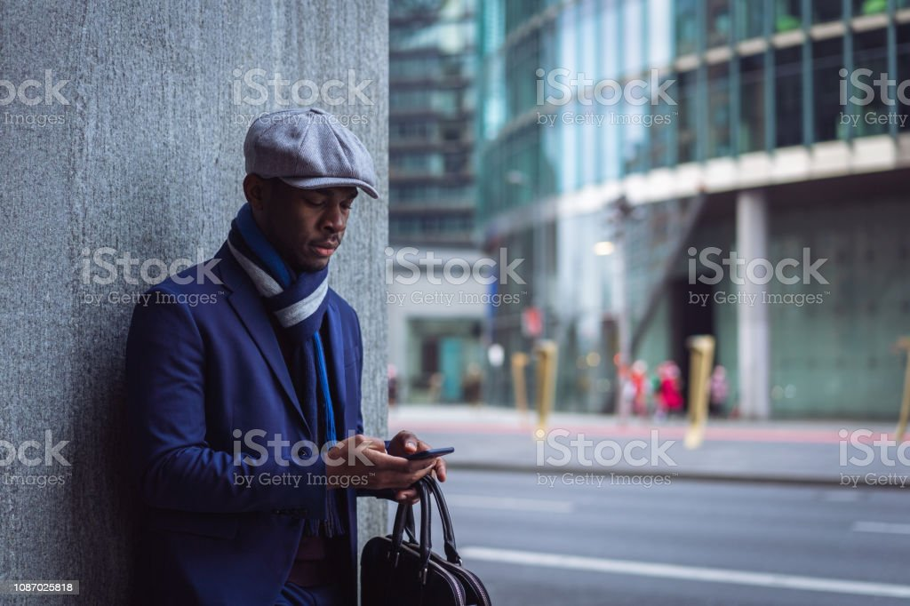 Businessman sending text message in the city Worried African man is standing leaned on the wall and texting message on smart phone in the city. 20-29 Years Stock Photo
