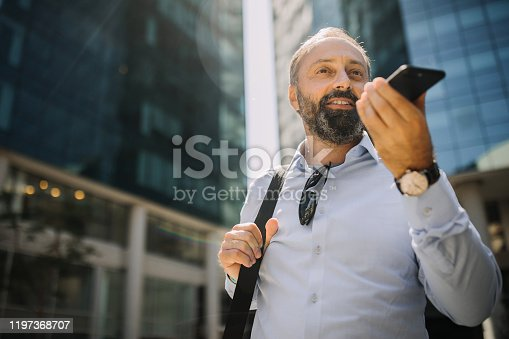 Businessman sending voice message while leaving business building