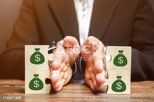 1145921132istockphoto Businessman separates the wooden puzzle with a picture of money. The concept of financial management and distribution of funds. Saving and investing. Property division. Divorce and legal services 1140571926