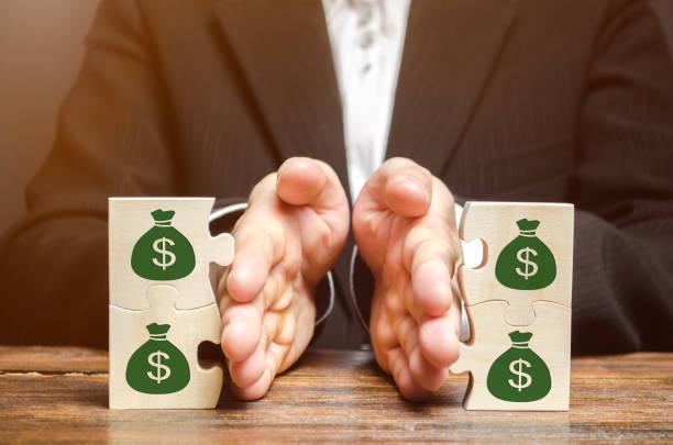 homme d'affaires sépare le puzzle en bois avec une image de l'argent. le concept de gestion financière et de distribution des fonds. épargner et investir. division immobilière. divorce et services juridiques - séparation photos et images de collection