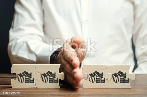 istock Businessman separates the wooden puzzle with a picture of money. The concept of financial management and distribution of funds. Saving and investing. Property division. Divorce and legal services 1153632719