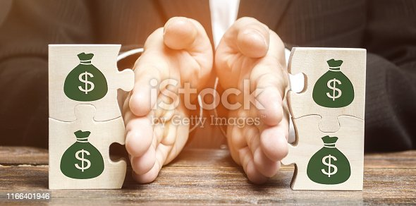 1145921132istockphoto Businessman separates the wooden puzzle with a picture of money. The concept of financial management and distribution of funds. Saving and investing. Property division. Divorce and legal services 1166401946