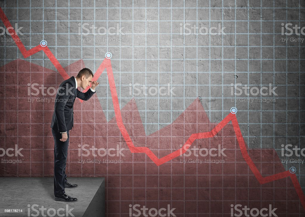 Businessman shading eyes with his hand looking at falling diagram stock photo