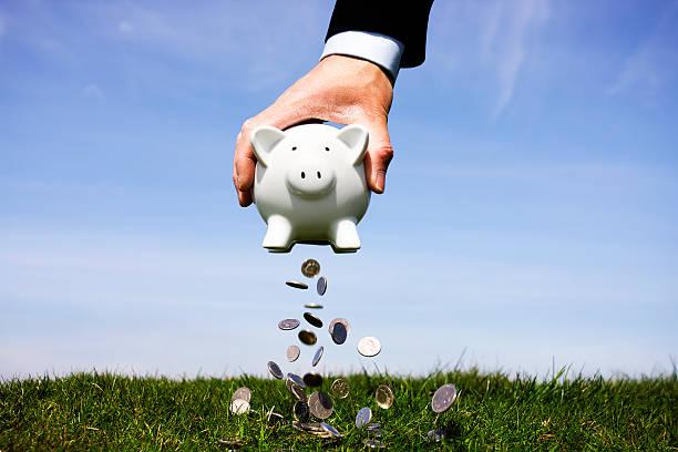 Businessman shaking a piggy bank stock photo