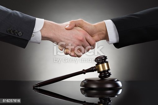 istock Businessman Shaking Hands In Front Of Mallet 516257616