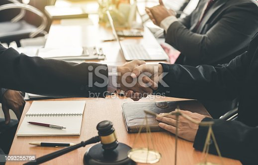 836113188 istock photo Businessman shaking hands to seal a deal with his partner lawyers or attorneys discussing a contract agreement. 1093255798