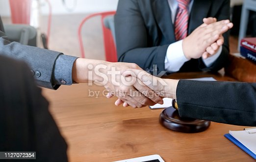 836113188 istock photo Businessman shaking hands to seal a deal with his partner lawyers or attorneys discussing a contract agreement. 1127072354