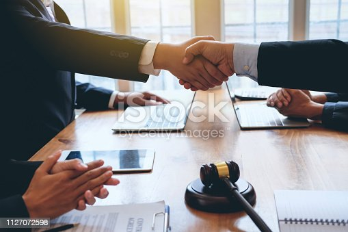 836113188 istock photo Businessman shaking hands to seal a deal with his partner lawyers or attorneys discussing a contract agreement. 1127072598