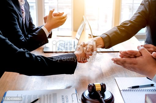 836113188 istock photo Businessman shaking hands to seal a deal with his partner lawyers or attorneys discussing a contract agreement. 1130456663