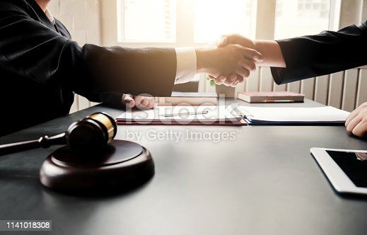 836113188 istock photo Businessman shaking hands to seal a deal with his partner lawyers or attorneys discussing a contract agreement and lawsuit. 1141018308