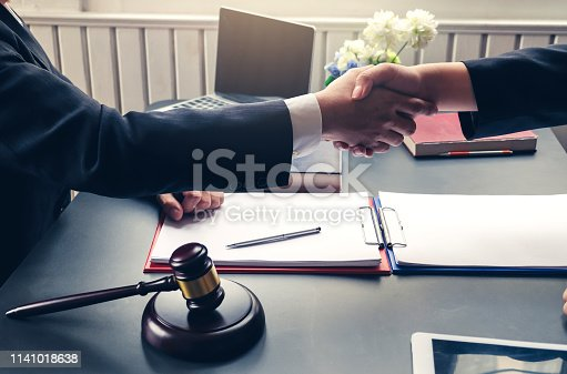 836113188 istock photo Businessman shaking hands to seal a deal with his partner lawyers or attorneys discussing a contract agreement and lawsuit. 1141018638