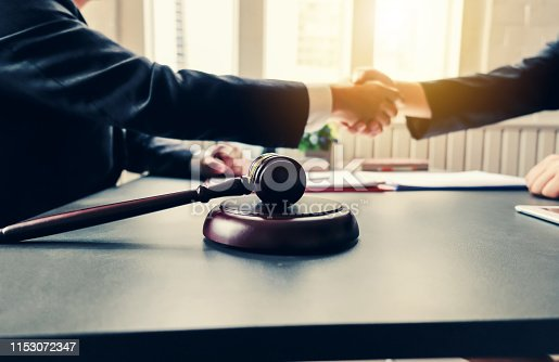 836113188 istock photo Businessman shaking hands to seal a deal with his partner lawyers or attorneys discussing a contract agreement and lawsuit. 1153072347