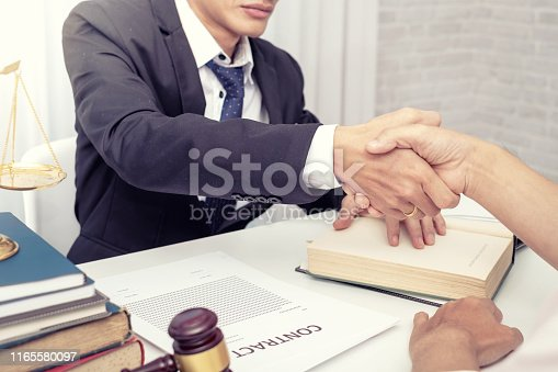 836113188 istock photo Businessman shaking hands to seal a deal with his partner lawyers or attorneys discussing a contract agreement. 1165580097