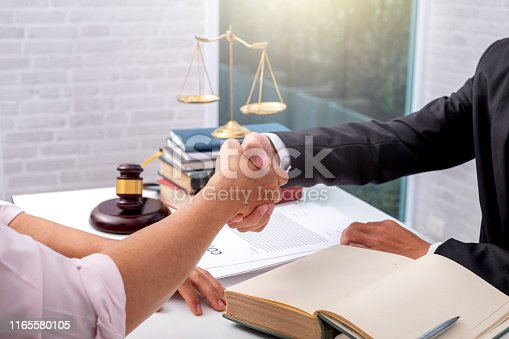 istock Businessman shaking hands to seal a deal with his partner lawyers or attorneys discussing a contract agreement. 1165580105