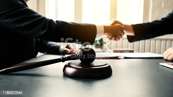 836113188 istock photo Businessman shaking hands to seal a deal with his partner lawyers or attorneys discussing a contract agreement. 1180522044