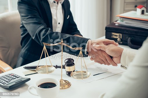 istock Businessman shaking hands to seal a deal with his partner lawyers or attorneys discussing a contract agreement 930579260