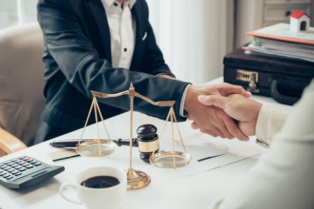 hombre de negocios dándose la mano para sellar un acuerdo con su socio abogados o abogados discutiendo un contrato - abogado fotografías e imágenes de stock