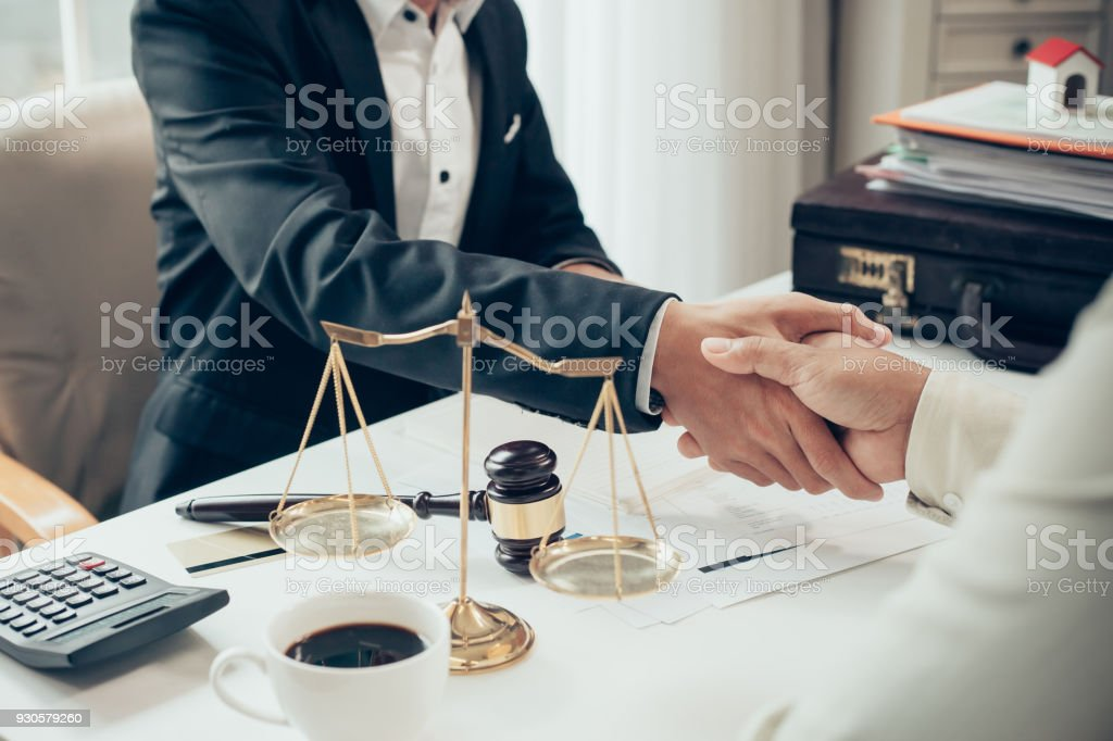 Businessman shaking hands to seal a deal with his partner lawyers or attorneys discussing a contract agreement stock photo