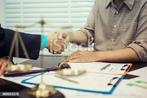 836113188 istock photo Businessman shaking hands to seal a deal with his partner lawyers or attorneys discussing a contract agreement 968953376