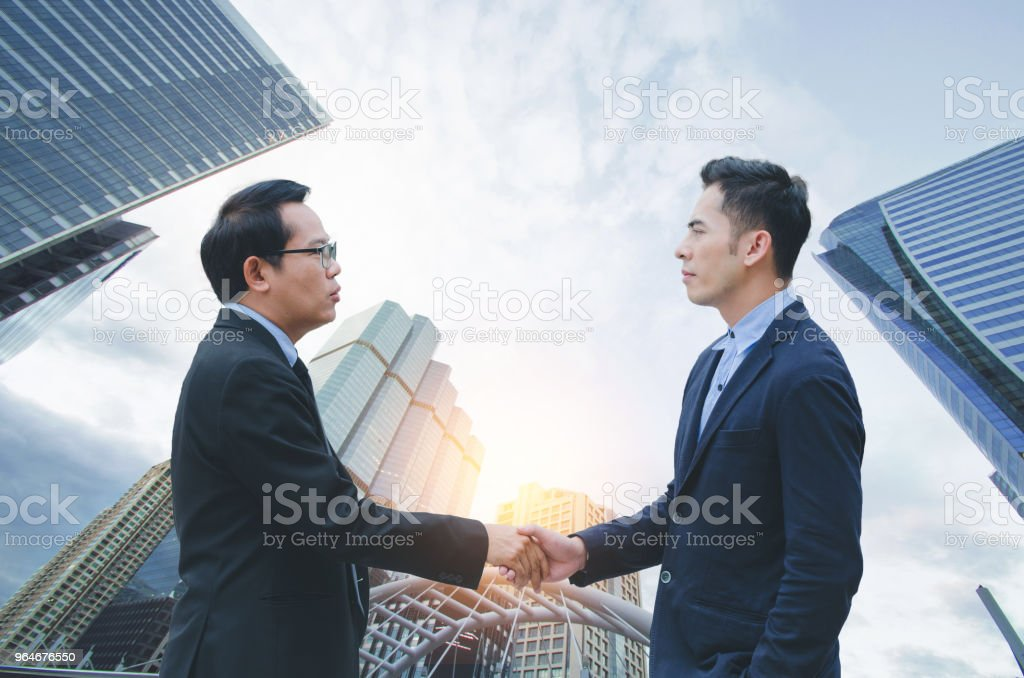businessman shaking hands under skyscraper view from high-rise building for complete business deal together successful. teamwork concept. partnership and dealership concept and property real estate. royalty-free stock photo