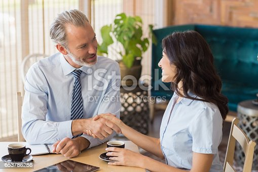 Businessman shaking hands with businesswoman while having a cup of tea at restaurant