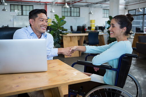 660681964 istock photo Businessman shaking hands with disabled colleague 657146934