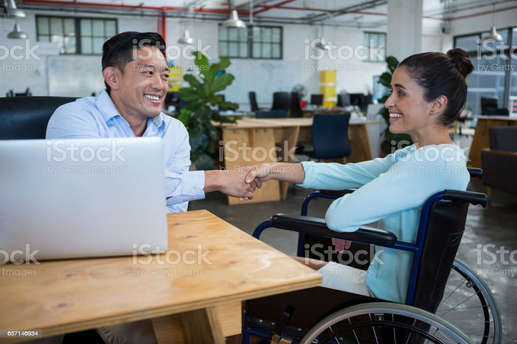 Businessman shaking hands with disabled colleague stock photo