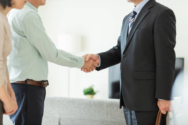 Businessman shaking hands with middle aged couple stock photo