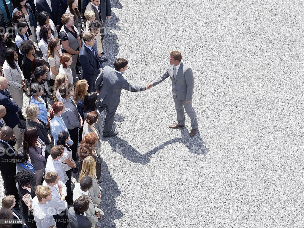 Businessman shaking mans hand in crowd stock photo