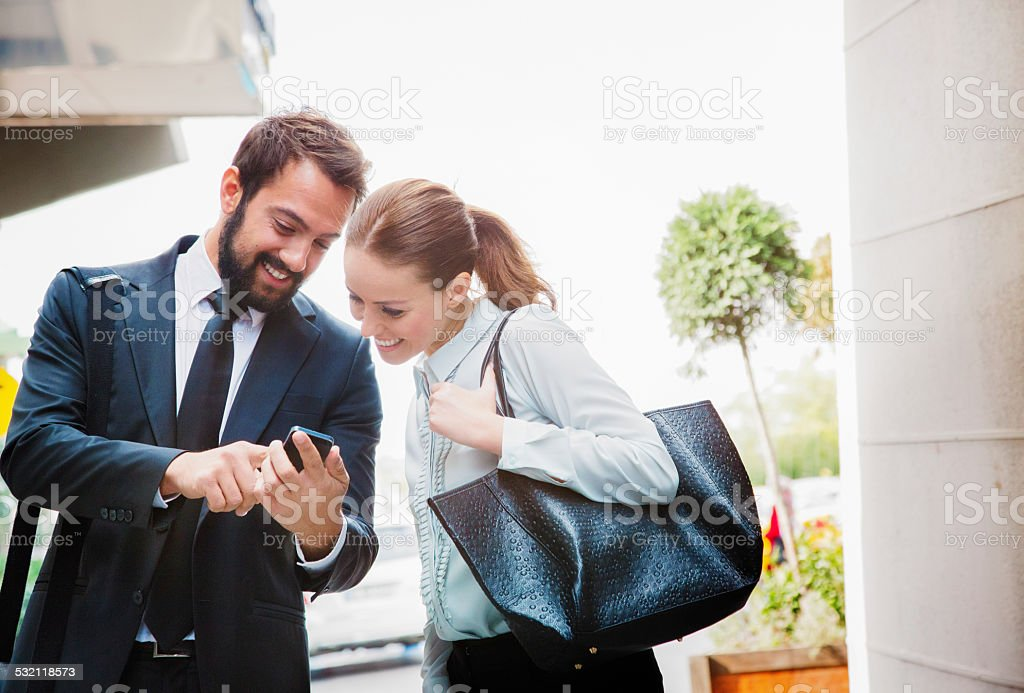 Businessman shares stock market results with colleague on mobile phone stock photo