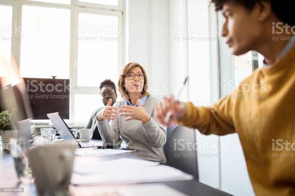 Businessman sharing her ideas in boardroom meeting stock photo