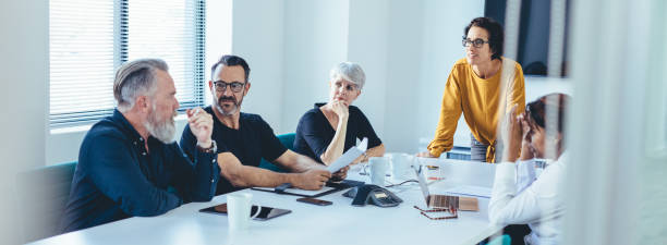 businessman sharing his ideas to colleagues - pensionati lavoratori foto e immagini stock