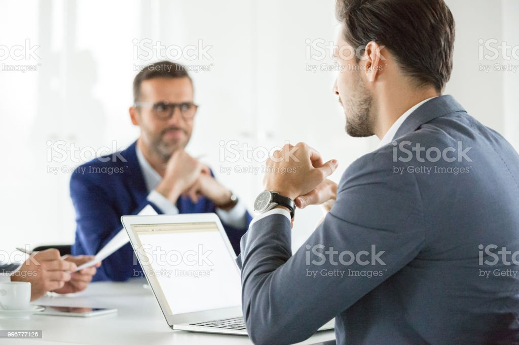 Businessman sharing his ideas with team in meeting Young businessman with laptop sharing his ideas with team in meeting. Business group having a meeting in office. Adult Stock Photo