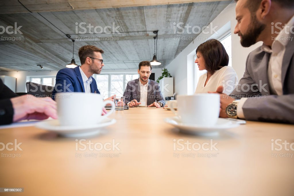 Businessman sharing ideas with colleagues in a meeting Young businessman sharing his ideas with colleagues in conference room. Business people discussing over new business plan in office. Adult Stock Photo
