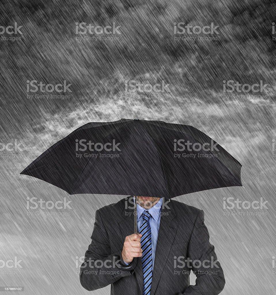 Businessman sheltering stock photo