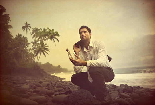 businessman shipwrecked on a desert island - desert island stock photos and pictures