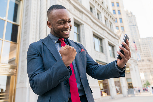 Businessman shooting selfie with phone in a successful winner pose