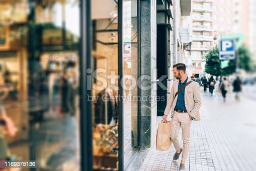 Businessman with shopping bag looking at shop window in the city