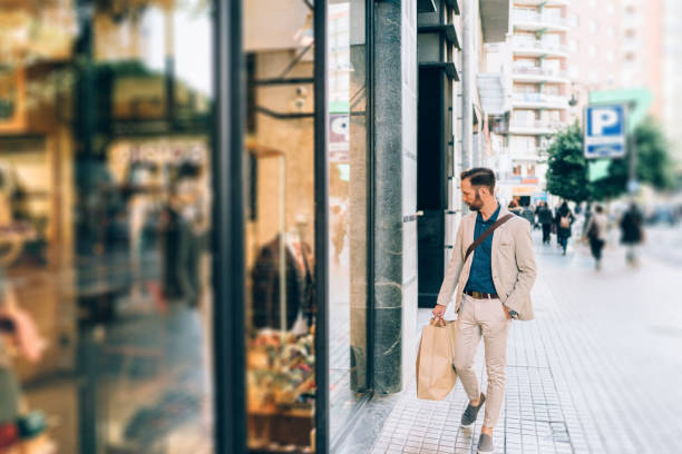 Businessman shopping in Valencia Businessman with shopping bag looking at shop window in the city boutique stock pictures, royalty-free photos & images