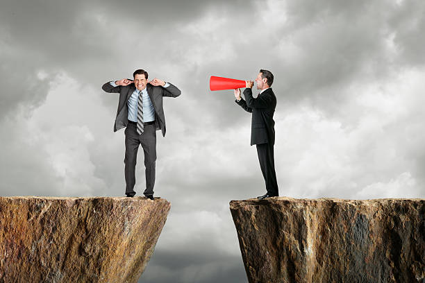 Businessman shouting at another businessman through a megaphone Businessman shouting at business person. hands covering ears stock pictures, royalty-free photos & images