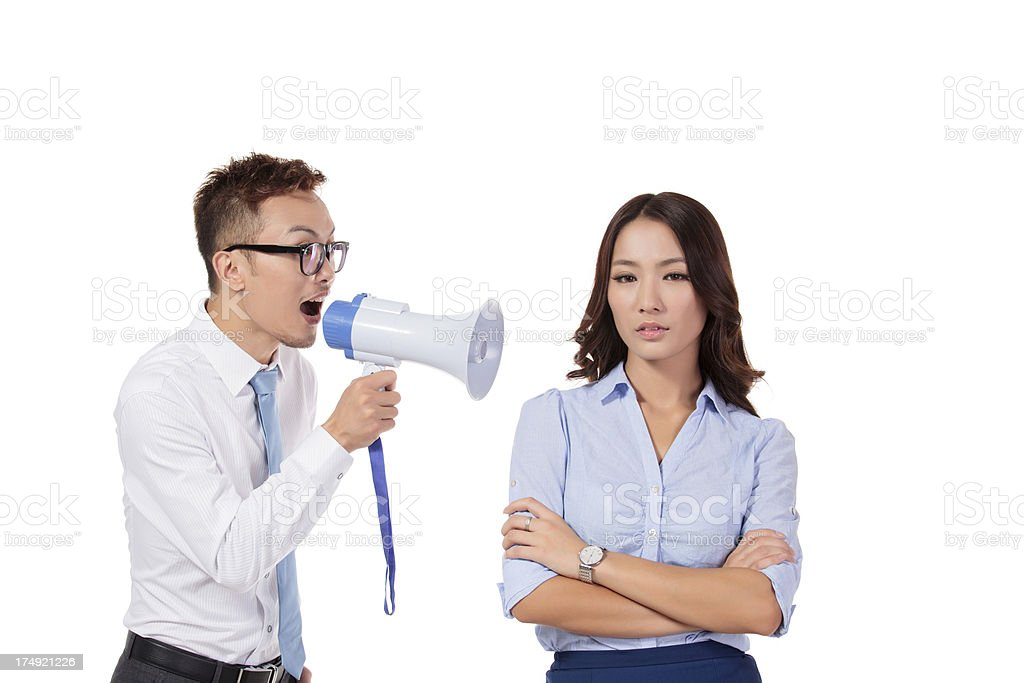 Businessman shouting in megaphone into businesswoman's ear stock photo