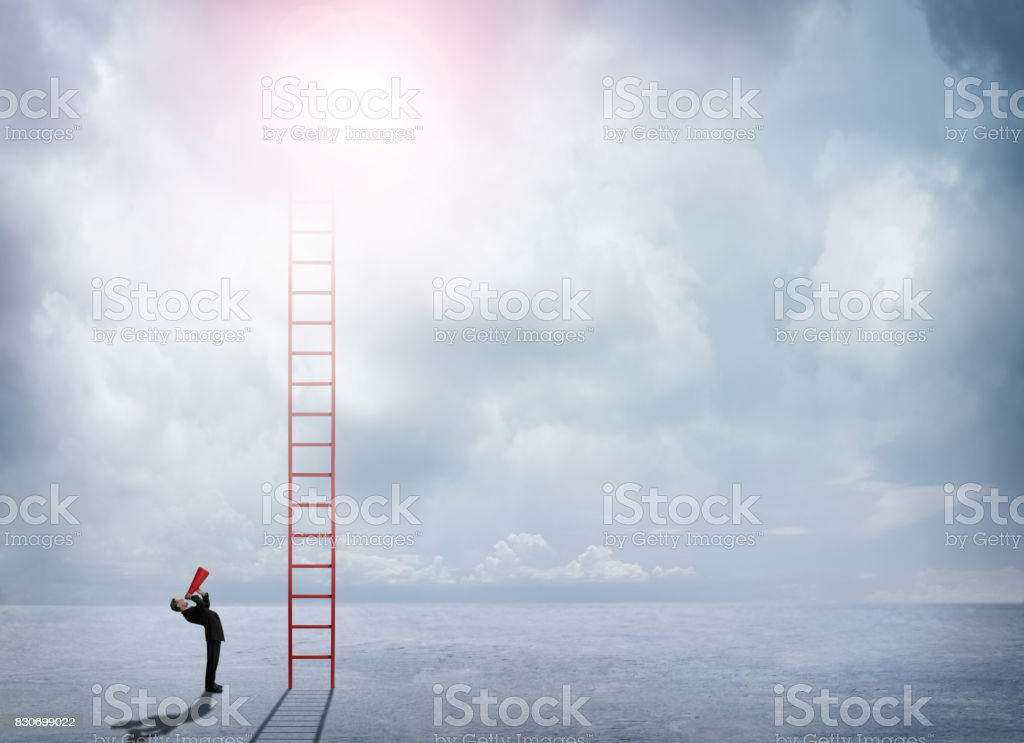 Businessman Shouts Up Toward Top Of Ladder That Extends Into Clouds stock photo