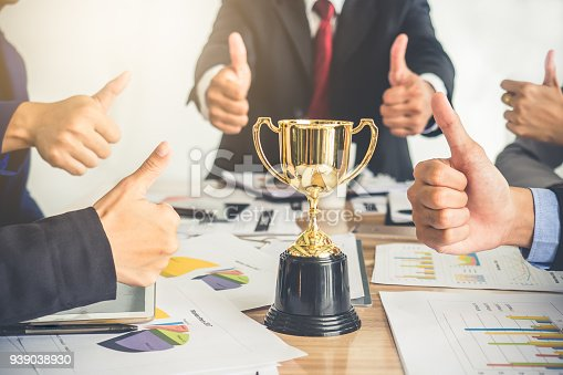 istock Businessman show thumbs up with trophy, reward, winner, champion and successful for business 939038930
