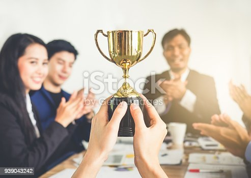 istock Businessman show thumbs up with trophy, reward, winner, champion and successful for business 939043242