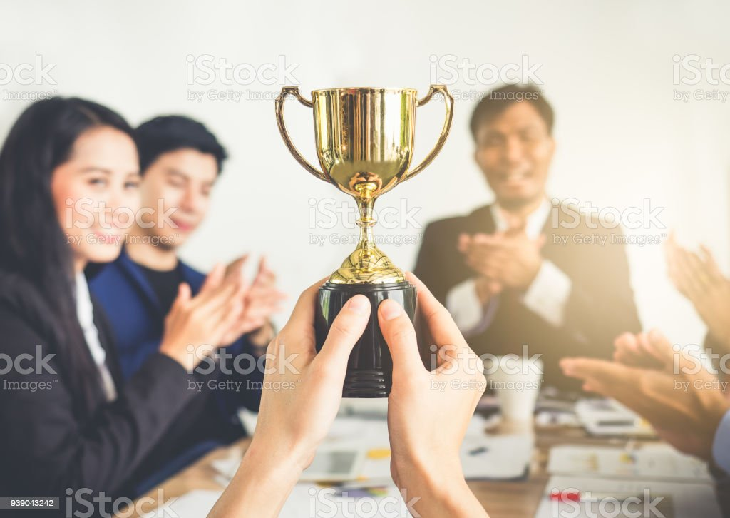 Businessman show thumbs up with trophy, reward, winner, champion and successful for business stock photo
