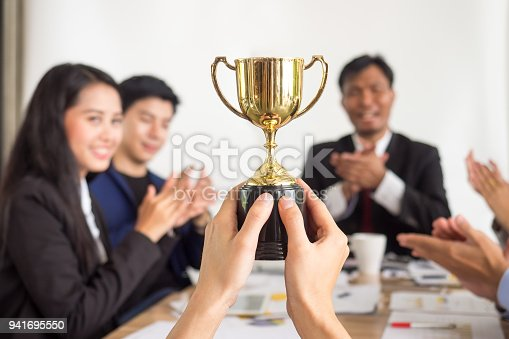 istock Businessman show thumbs up with trophy, reward, winner, champion and successful for business 941695550