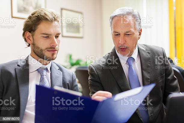 Businessman Showing A Document To His Colleague Stock Photo - Download Image Now
