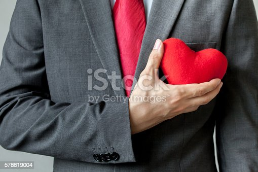 istock Businessman showing compassion holding red heart onto his chest 578819004