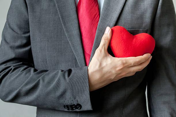 businessman showing compassion holding red heart onto his chest - gute geschenke stock-fotos und bilder